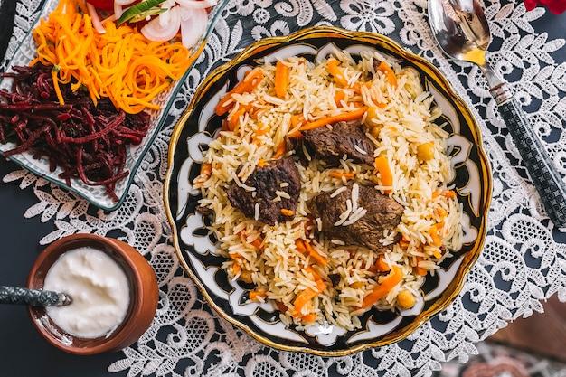 Вид сверху риса с морковью, приготовленной с бараниной, подается с йогуртом и салатом Бесплатные Фотографии