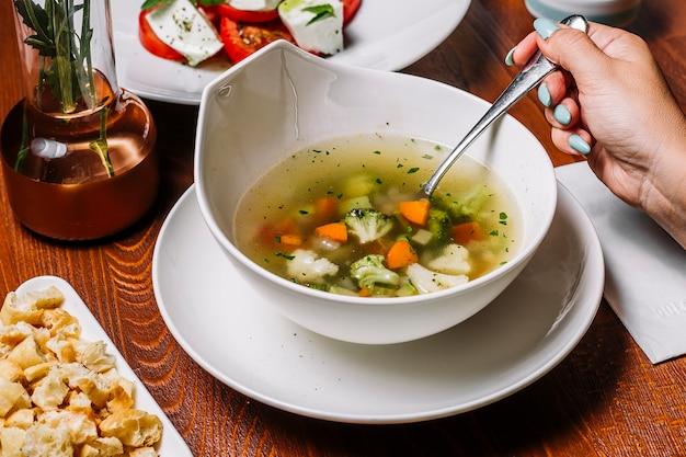 女性はブロッコリーエンドウニンジンセロリとジャガイモと野菜のスープを食べる 無料写真