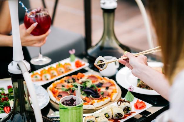 Женщина принимает суши с палочкой для еды на ужин Бесплатные Фотографии