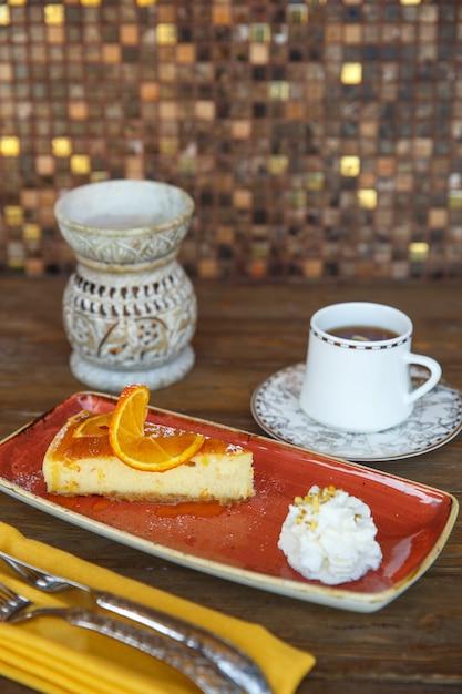 オレンジチーズケーキとクリーム、紅茶添え 無料写真