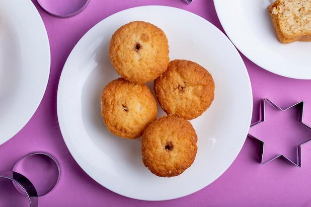 Вид сверху кексы на белой тарелке на фиолетовый Бесплатные Фотографии