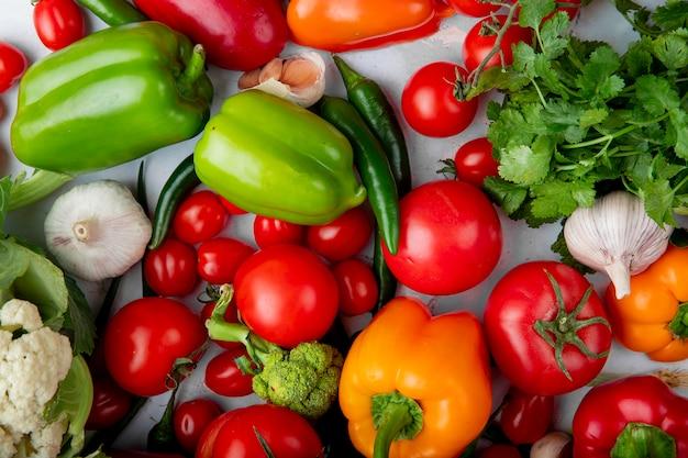 白い背景の上のトマトカラフルなピーマン緑唐辛子ニンニクネギとブロッコリーとして新鮮な熟した野菜のトップビュー 無料写真