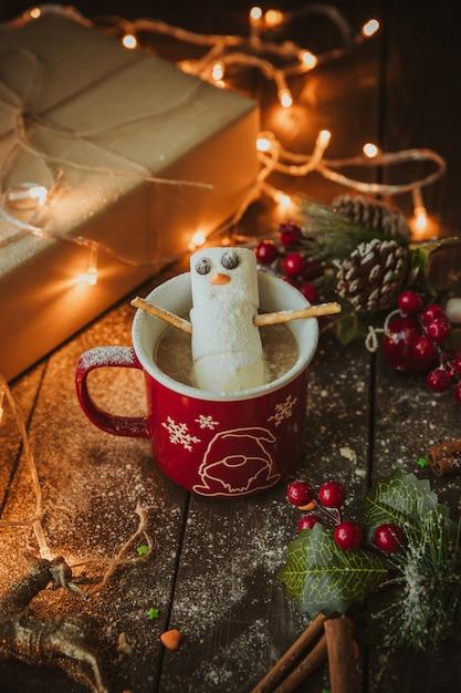 クリスマステーブルの上のコーヒーマグカップで雪だるま 無料写真