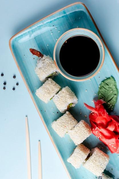 ゴマとサイドソースをトッピングした巻き寿司 無料写真