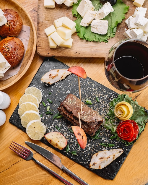 トップビューロールレモンスライスと赤ワインのガラスの肉 無料写真