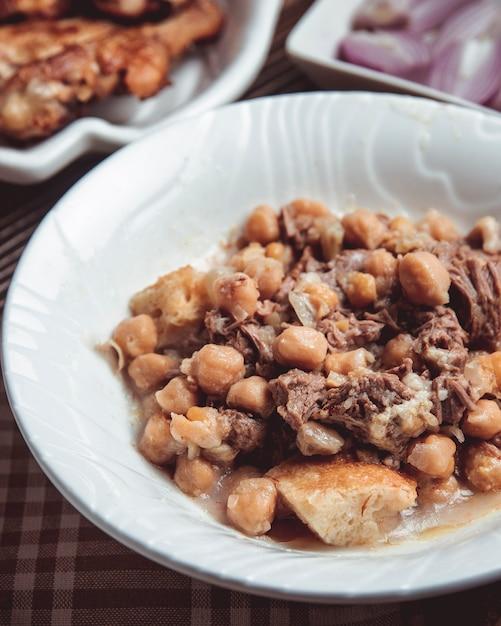 ラム、ファットラム、栗、エンドウ豆と一緒に白い皿に同情 無料写真