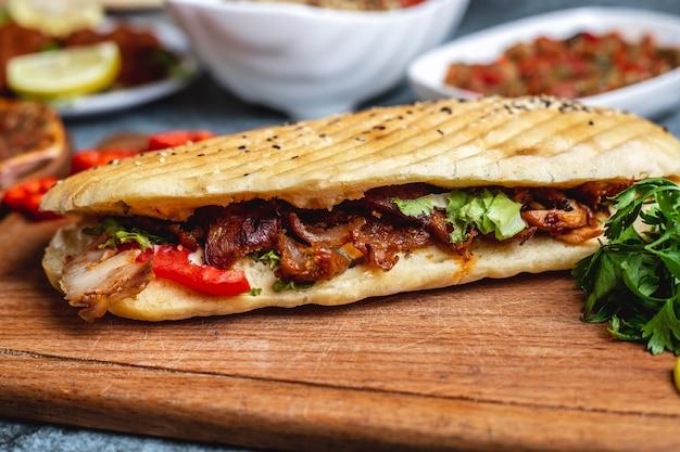Вид сбоку куриный донер с томатной зеленью и салатом в хлебе Бесплатные Фотографии