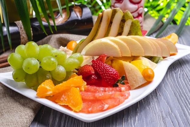 側面図フルーツプレートオレンジいちごバナナキウイ梨ブドウとチェリープラム 無料写真