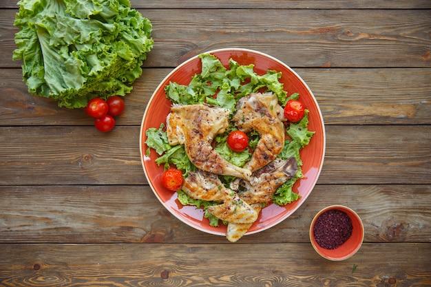 チェリートマトのレタスの葉で焼いた鶏のグリル脚のトップビュー 無料写真