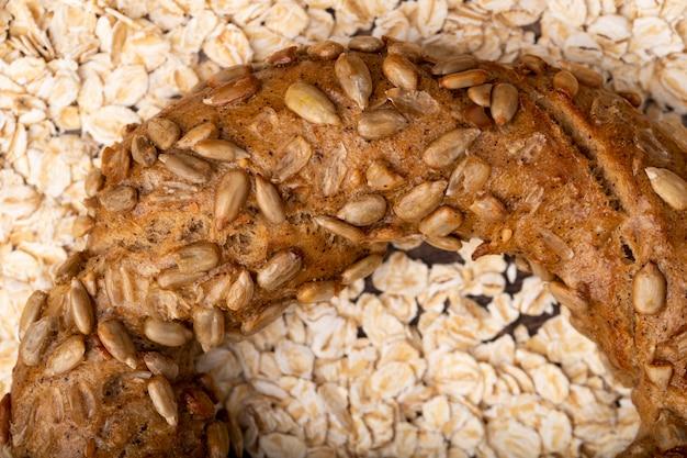 オート麦の背景にベーグルのヒマワリの種のクローズアップビュー 無料写真