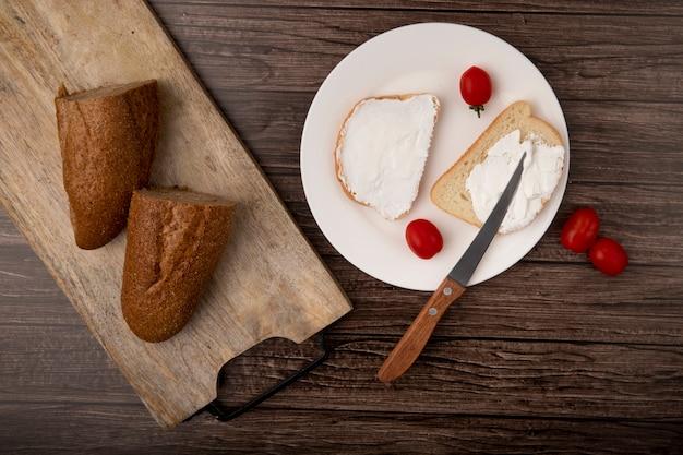 まな板の上半分のバゲットでカットされたパンのトップビューと木製の背景にトマトとナイフでスライスした白パンのプレート 無料写真