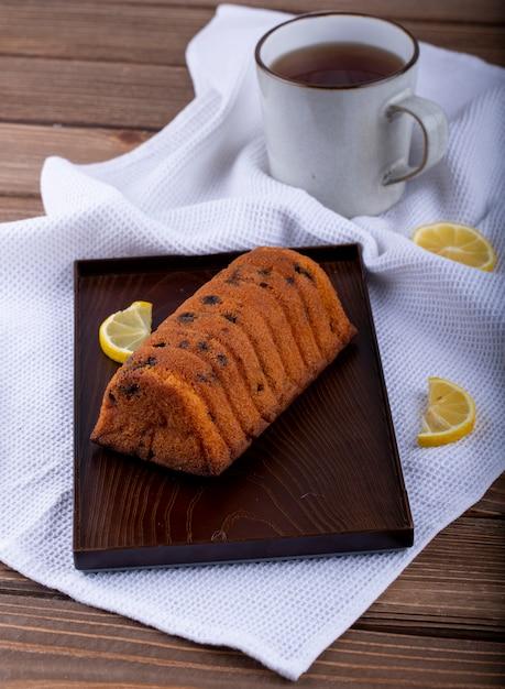 Вид сбоку торт с изюмом и дольками лимона на деревянной доске и кружка чая на скатерть Бесплатные Фотографии