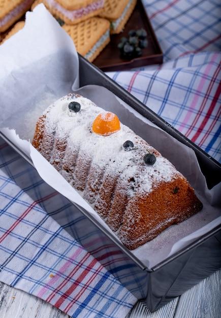 Вид сбоку торта с изюмом и сахарной пудрой на скатерть Бесплатные Фотографии