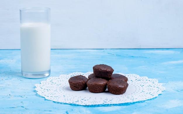 青のミルクのガラスを添えてチョコレートのマフィンの側面図 無料写真