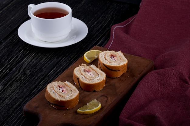 Вид сбоку ломтиков швейцарского ролла с малиновым вареньем на деревянной доске, подается с чашкой чая Бесплатные Фотографии