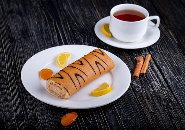 Вид сбоку рулет с абрикосовым джемом на белой тарелке подается с чашкой чая на деревенском Бесплатные Фотографии