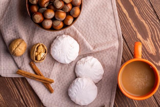 木製の白いゼファーマシュマロヘーゼルナッツとココアのマグカップのマグカップの上から見る 無料写真
