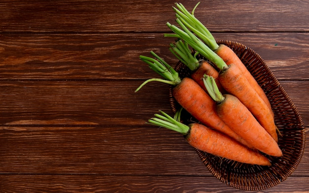 Вид сверху корзина с морковью на деревянном фоне с копией пространства Бесплатные Фотографии