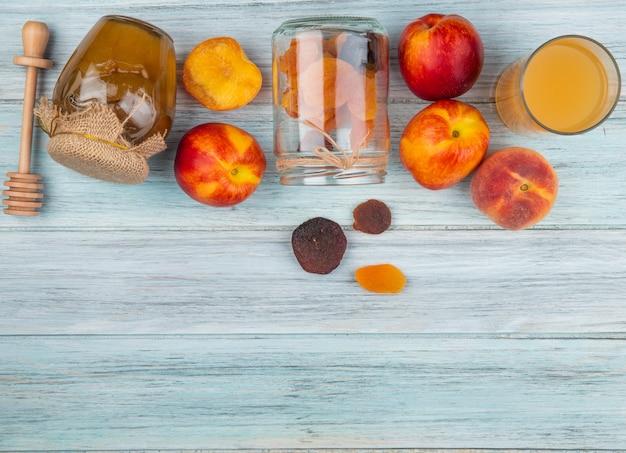 Вид сверху свежих спелых нектаринов с курагой, разбросанных от стеклянной банки меда в банке и стакан персикового сока на деревенском фоне с копией пространства Бесплатные Фотографии