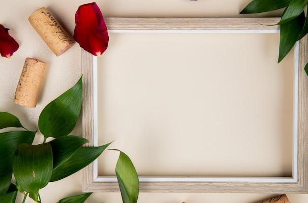 Крупным планом вид рамы с пробками на белом украшен листьями и лепестками цветов с копией пространства Бесплатные Фотографии