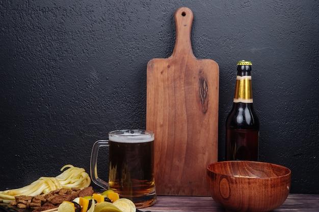 Вид сбоку на кружку пива с деревянной разделочной доской, бутылку пива и различные соленые закуски на черном Бесплатные Фотографии