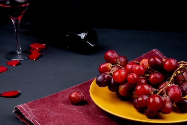 Вид сбоку тарелки с виноградом на ткани со стеклом и бутылка красного вина с лепестками цветов на черном Бесплатные Фотографии