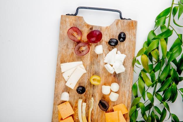 Вид сверху различных видов сыра с кусочками винограда и оливок на разделочной доске на белом украшенный листьями с копией пространства Бесплатные Фотографии