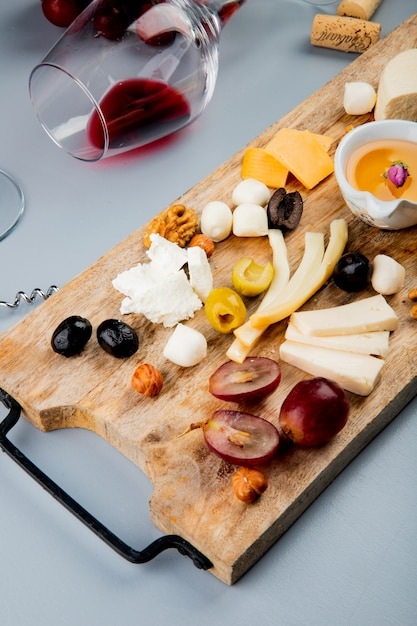 まな板と白のコルクのチーズグレープオリーブナッツバターのさまざまな種類の赤ワインのガラスを横になっているの平面図 無料写真
