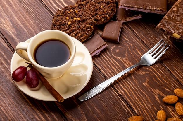 木製の背景にチョコレートバーとコーヒーのカップとフォークでオートミールクッキーの側面図 無料写真