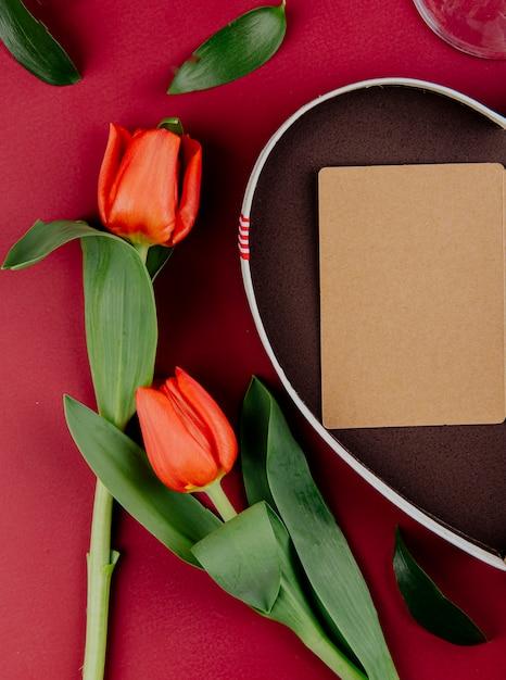 赤い背景に開いているポストカードとハート型のギフトボックスと赤い色のチューリップの花のトップビュー 無料写真