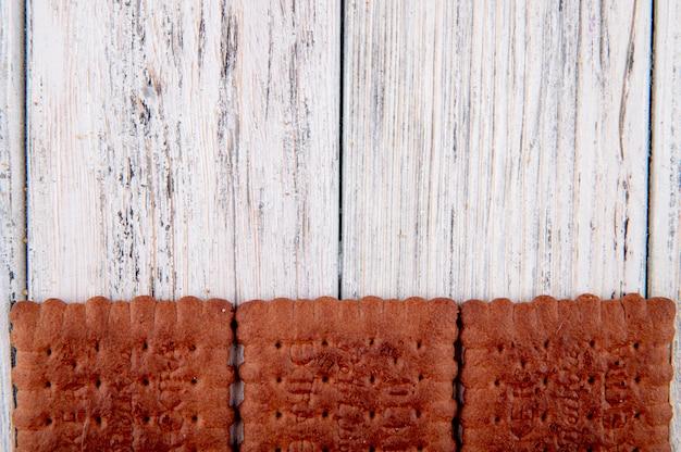 白い木製の背景にコピースペースが付いている下部にトップビューチョコレートクラッカー 無料写真