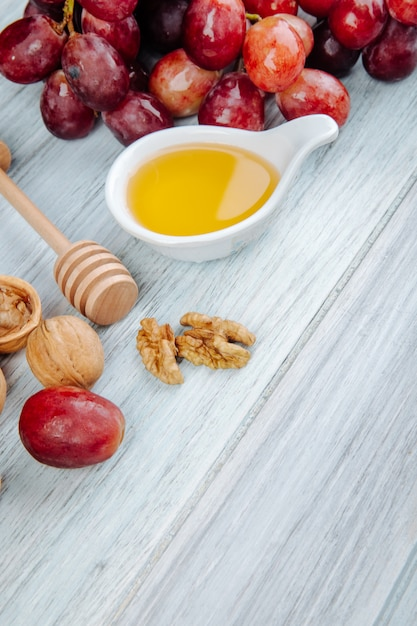 Вид сбоку меда с деревянной ложкой меда, свежим виноградом и грецкими орехами на сером деревянном столе Бесплатные Фотографии