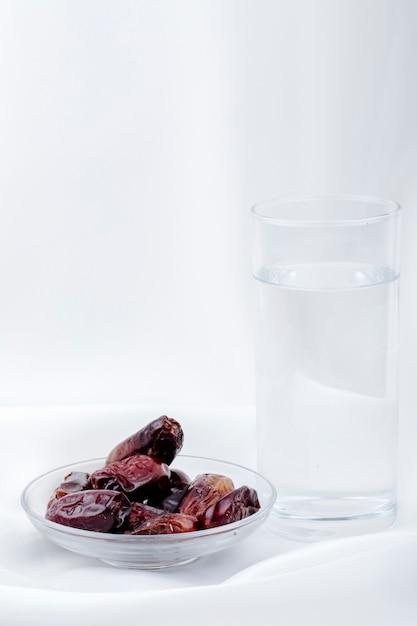 Вид сбоку сладких сушеных фиников в блюдце со стаканом воды на белом фоне Бесплатные Фотографии