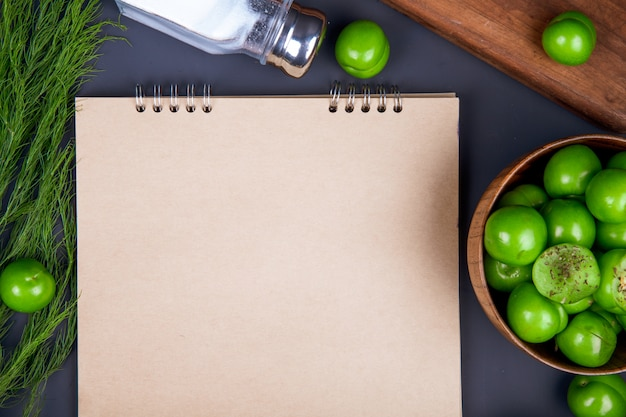 黒いテーブルに木製のボウルにスケッチブック、塩入れ、フェンネル、サワーグリーンプラムの平面図 無料写真
