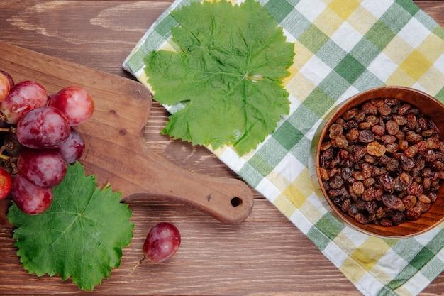 Вид сверху свежего сладкого винограда на деревянной разделочной доске, зеленые виноградные листья и изюм в миску на клетчатой ткани на деревянный стол Бесплатные Фотографии