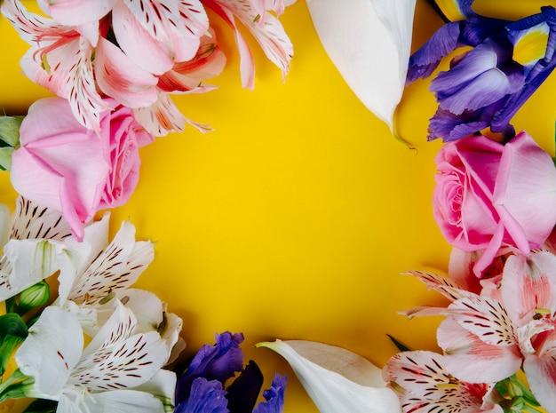 コピースペースと黄色の背景に美しい花ピンクのバラアルストロメリアダークパープルアイリスと白いカラーリリー色で作られたフレームのトップビュー 無料写真