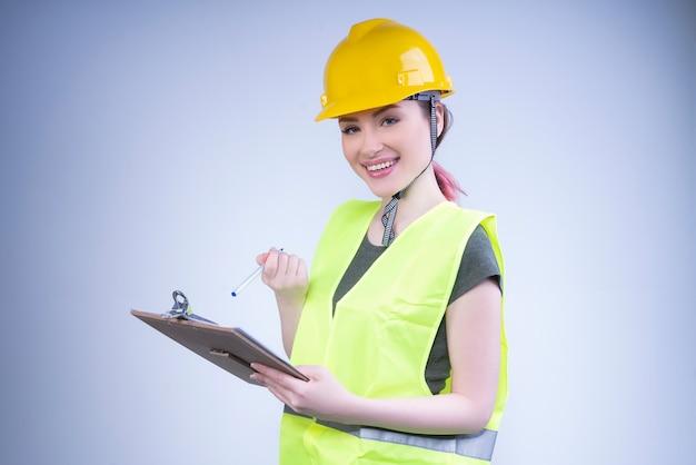 Улыбающаяся женщина-инженер в желтом шлеме делает записи Бесплатные Фотографии