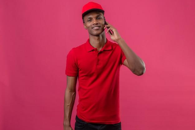 Молодой афроамериканец доставляющий носить красную рубашку поло и шапку, глядя уверенно и говорить с помощью смартфона на изолированных розовый Бесплатные Фотографии
