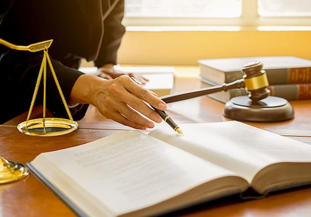 法律事務所の背景でチームミーティングを持つ弁護士と弁護士を裁く。 Premium写真