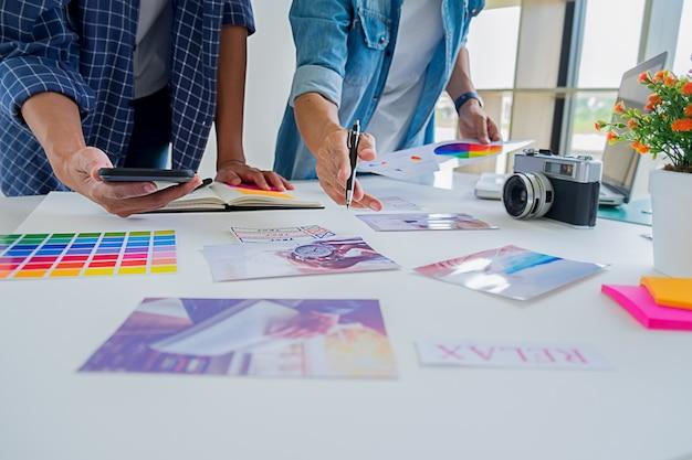 アジアの広告デザイナーの創造的なスタートアップチームがオフィスでアイデアを議論します。 Premium写真