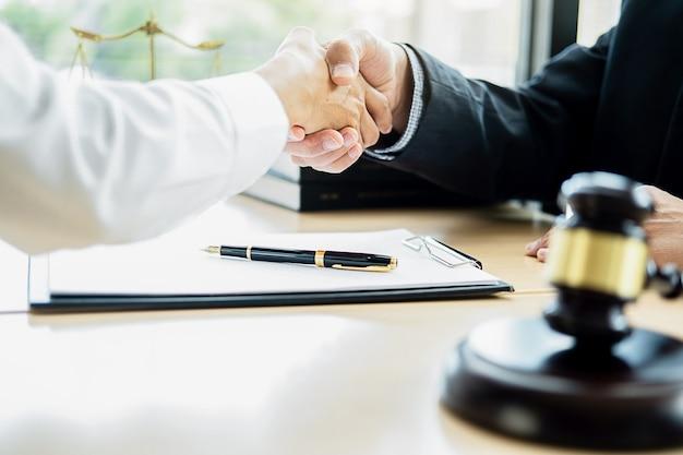 法律事務所の背景を持つ法律事務所でチーム会議を行っている正義の弁護士と小槌を判断します。 Premium写真