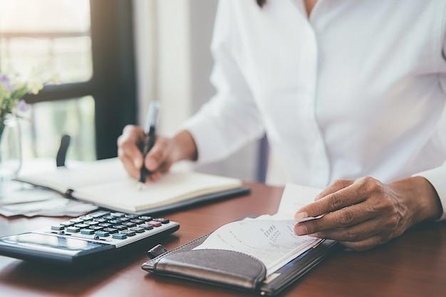請求書と電卓を持つ女性。電卓を使用してオフィスのテーブルで請求書を計算する女性。 Premium写真