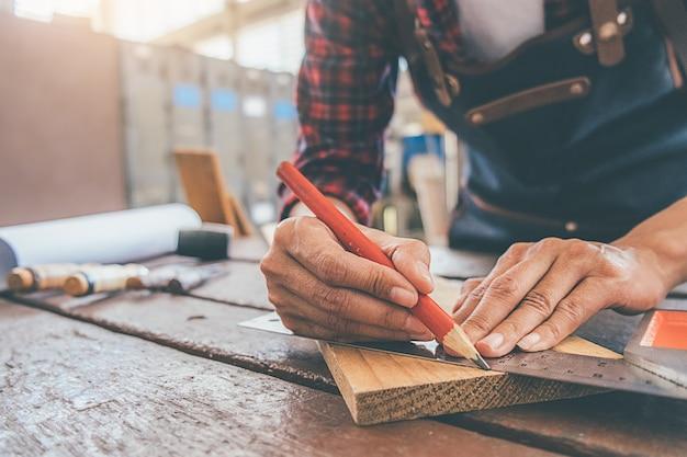 大工は大工仕事の木製テーブルの上の機器での作業します。 Premium写真