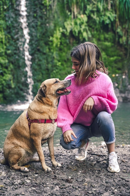 Молодая девушка с ее собакой гуляя в природу Premium Фотографии