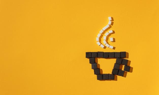 黄色の背景に石炭と砂糖キューブで作られた蒸気でコーヒーカップ。 Premium写真