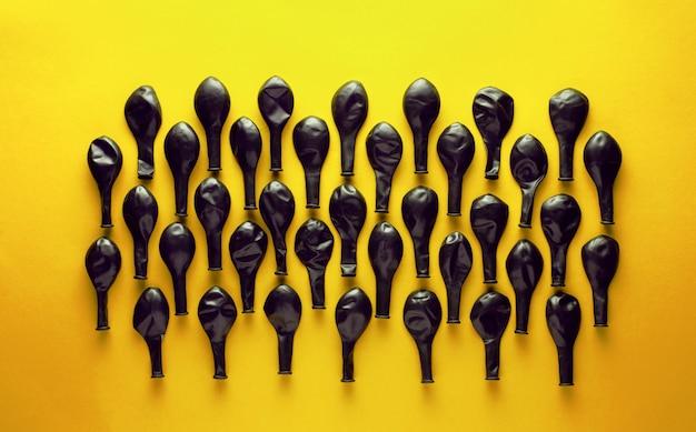黄色の背景に黒の収縮バルーン。 Premium写真