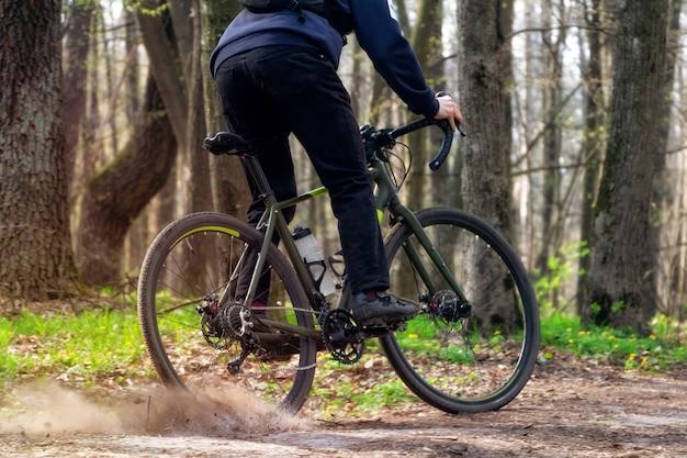 Велосипедист на гравийном велосипеде. велосипедист едет по лесной тропе, дрейфующей с задним колесом и поднимающей поле. Premium Фотографии