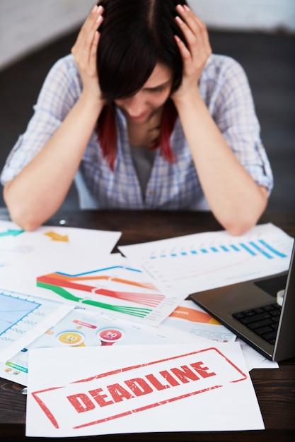 Утомленная нарушенная работница с головной болью. усиленная женщина в офисе держа голову в руках и думая о крайнем сроке Premium Фотографии