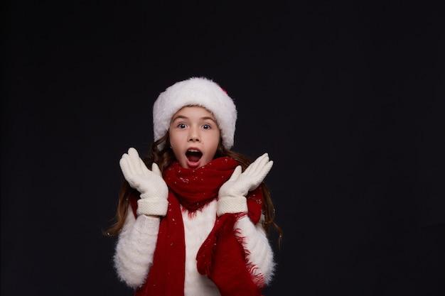 Портрет молодой красивой улыбающейся девушки в красной шапке санты на темном фоне Premium Фотографии