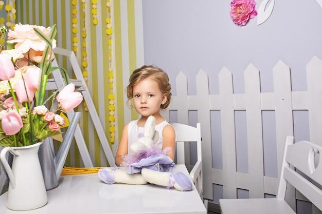 おもちゃを演奏する美しい少女。青い目のブロンド。 Premium写真